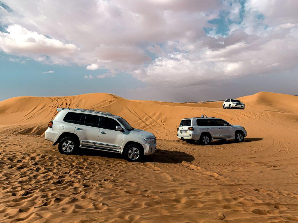 dubai desert safari three white SUVS in the sand